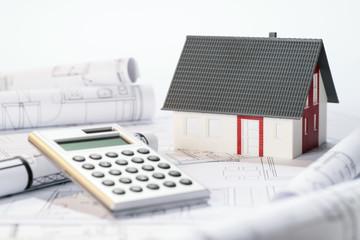 Architekturmodell, Taschenrechner und Baupläne