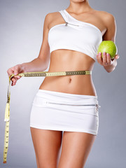 Healthy female body with apple and measuring tape.