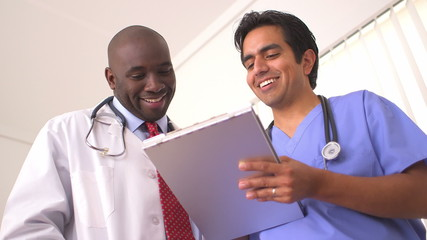 Hispanic and African American doctors reviewing medical charts