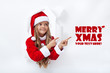 Santa girl pointig to copy space - leaning through hole in paper