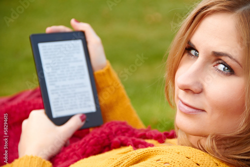 woman is reading the e-book lying on the hammock