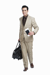 Businessman walking with holding passport and luggage bag