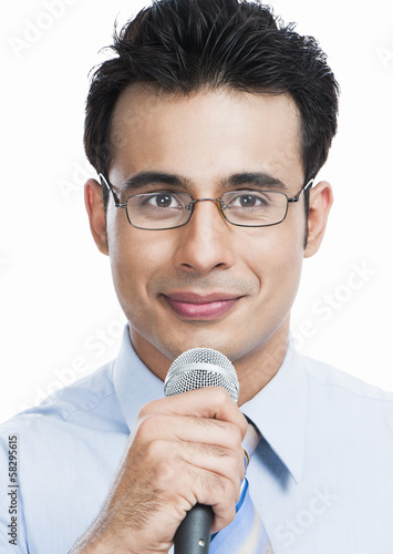 Portrait of a businessman holding a microphone