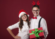 Smiling nerd couple holding red christmas gift