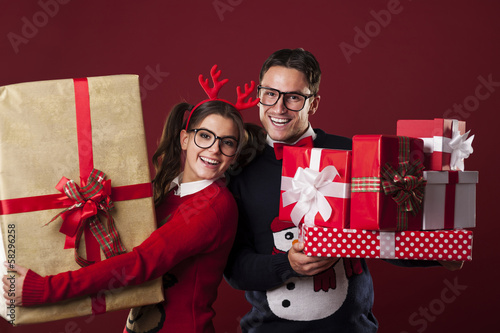 Happy nerd couple holding a lot of christmas presents