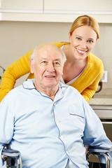 Pflegehilfe bei Senior im Rollstuhl