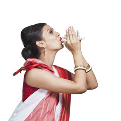 Traditional Bengali woman blowing shankha