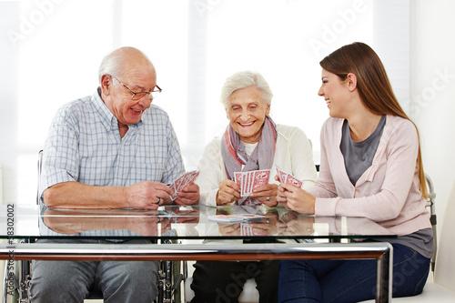 Frau spielt mit Senioren Karten im Pflegeheim