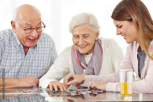 Leinwanddruck Bild Glückliches Paar Senioren spielt Puzzle