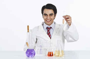 Male scientist working in a laboratory and smiling