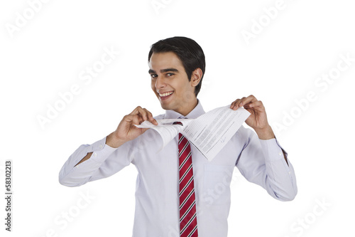 Businessman tearing a paper and smiling