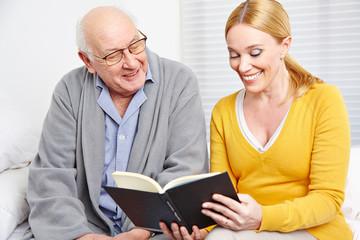 Frau liest Senior Geschichten aus Buch vor