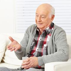 Senior zu Hause nimmt Medikamente ein