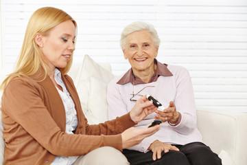 Frau misst Blutzuckerspiegel bei Seniorin