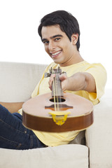 Portrait of a happy man holding a mandolin and smiling