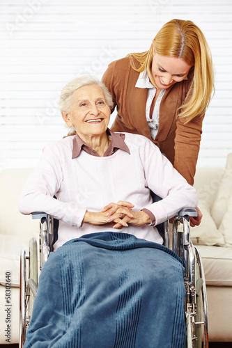 Seniorin im Rollstuhl wird von Tochter betreut