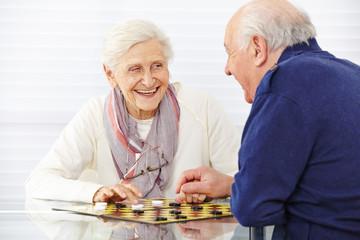 Seniorenpaar spielt Dame im Seniorenheim