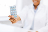 female doctor hand giving pack of pills