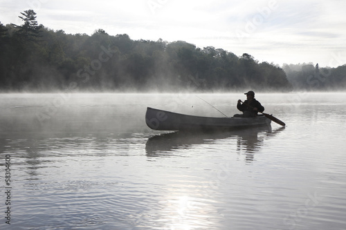 Fisherman Canoeing on a Misty Lake
