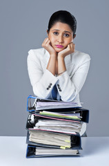 Businesswoman leaning on a stack of files and looking worried