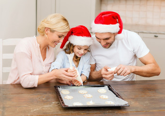 happy family in santa helper hats making cookies