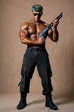 A muscular man with a gun in full view.