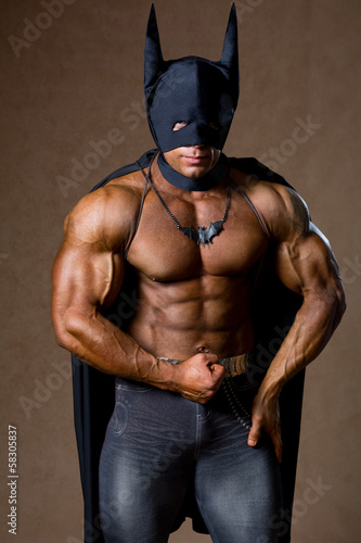 A muscular man in a Batman costume.