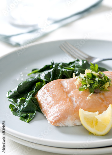 Closeup of poached salmon with vegetable relish and spinach.