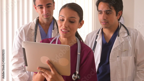 Team of Hispanic doctors working on a tablet