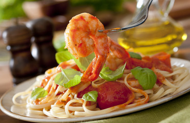Closeup of shrimp with pasta, tomato sauce and basil.