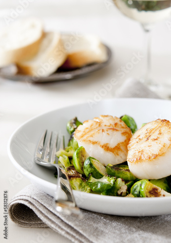 seared scallops with roasted Brussels sprouts and nuts. - 58312876