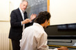 Student playing the piano with his teacher