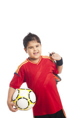 Boy carrying a soccer ball and his shoes
