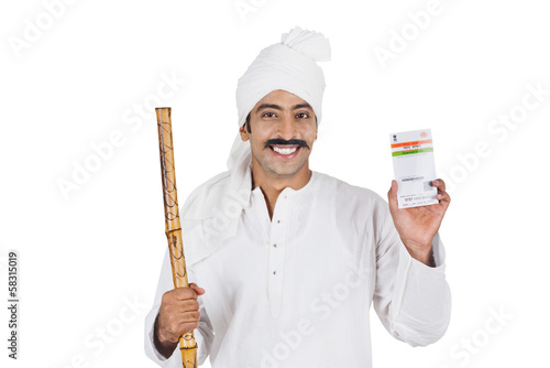Portrait of a man showing an Aadhaar Card and smiling