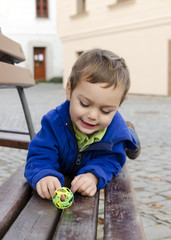 Child playing on city bench