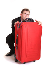 Distrustful business man behind red luggage