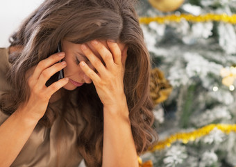 Portrait of stressed woman in front of christmas tree