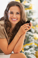 Portrait of happy woman with cell phone near christmas tree