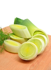 Fresh sliced leeks and dill on a wooden board