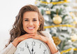 Smiling young woman showing clock in front of christmas tree