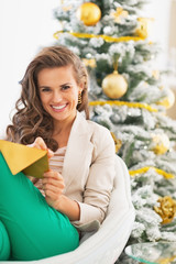Happy young woman writing on envelope near christmas tree