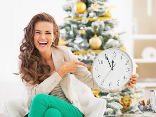 Happy young woman pointing on clock in front of christmas tree