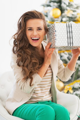 Excited young woman with christmas shaking present box