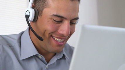 Friendly Hispanic telemarketer working at computer