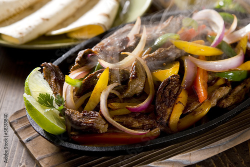 Steaming hot steak fajita in a cast iron skillet.