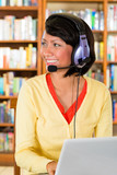 Young Girl in library with laptop and headphones