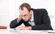 Managerkrankheit Burnout - Mann erschöpft und gestresst im Büro