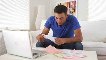 Hispanic man stressed while paying bills