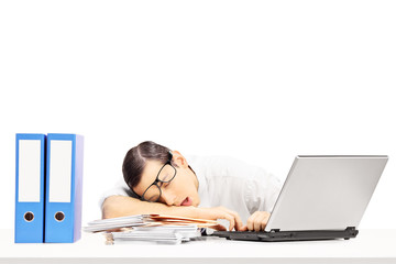 Exhausted young businessman sleeping on a desk at his workplace