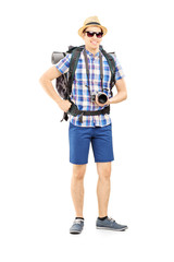 Male tourist with backpack and camera posing